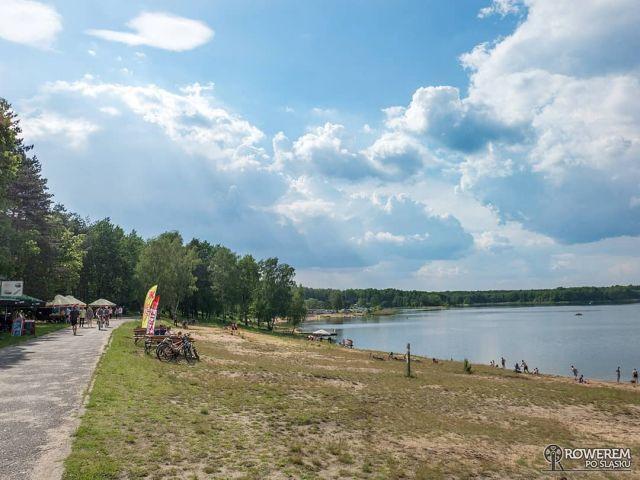 #KręćDo JEZIORO CHECHŁO-NAKŁO Sztuczny zbiornik wodny położony w powiecie tarnogórskim, na terenie gminy Świerklaniec. Pełni ono wiele funkcji rekreacyjnych. Wokół niego ośrodki wypoczynkowe, kempingi, wypożyczalnie kajaków, łodzi, rowerów wodnych a także liczne punkty gastronomiczne.  Rowerowo jest bardzo ciekawie! Dookoła jeziora biegnie Leśno Rajza czyli szlak rowerowy poprowadzony głównie przez tereny leśne. Szlak ten jest jednym z najbardziej lubianych przez śląskich rowerzystów, a odcinek z jeziora Chechło-Nakło do Parku w Świerklańcu idealnym na wycieczki rowerowe z dziećmi. Co ważne, nad jeziorem Chechło-Nakło znajduje się punkt odbioru gadżetów Rowerem po Śląsku! Odbierzecie je oczywiście w Barze u Adika! Jeśli natomiast po gadżety macie za daleko to poproście o nie tutaj: https://bit.ly/2ORe1ne  ...a no i te samoloty :) Więcej informacji o samej miejscówce oraz trasach dojazdowych znajdziecie na blogu: https://roweremposlasku.pl/jezioro-chechlo-naklo/ #rowerempośląsku #roweremposlasku #śląsk #slaskietravel #silesia #lovesilesia #natura #naturelovers #wycieczka #wycieczkarowerowa #tripbike #jezioro #jeziorochechłonakło #zbiornikwodny #leśnorajza #szlakirowerowe #odpoczynek #polskajestpiekna #rowerowo #rowerowelove